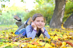 Little girl lays on the leaves Royalty Free Stock Images