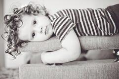 Little girl lays on a sofa. Stock Photos