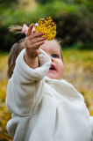 A little girl with a leaf Royalty Free Stock Image