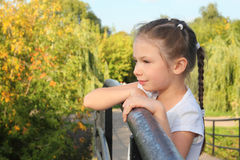 Little girl is lean elbow on bridge fence Royalty Free Stock Photos