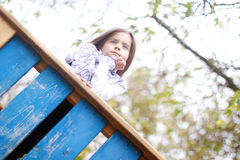 Little girl leaned on the wooden fence Stock Photo