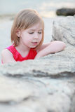A little girl leaning against a white stone Stock Photography