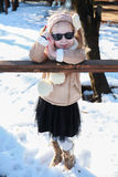 A little girl leaning against a wooden railing in winter park Stock Photo