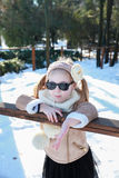 A little girl leaning against a wooden railing in winter park Royalty Free Stock Photography