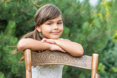 Little girl is leaning on an old wooden chair Royalty Free Stock Image