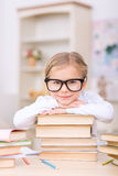 Little girl leaning on a pile of books Stock Image