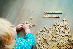 Little girl play with letter puzzle in school or daycare Royalty Free Stock Photography