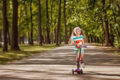 Little girl learn to ride scooter in a park on sunny summer day. Royalty Free Stock Photography