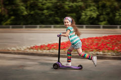 Little girl learn to ride scooter in a park on sunny summer day. Royalty Free Stock Images