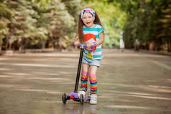Little girl learn to ride scooter in a park on sunny summer day. Stock Photography