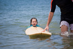 Little girl learn to surf at ocean. The Little girl learn to surf at ocean stock images