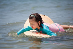 Little girl learn to surf at ocean. The Little girl learn to surf at ocean stock image