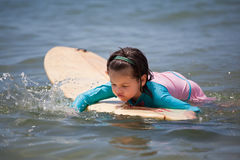 Little girl learn to surf at ocean. The Little girl learn to surf at ocean royalty free stock photos
