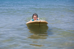 Little girl learn to surf at ocean. The Little girl learn to surf at ocean royalty free stock images