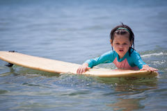Little girl learn to surf at ocean. The Little girl learn to surf at ocean stock photography