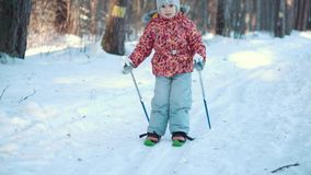 A little girl is learning cross country skiing. In the forest. Medium long shot stock footage