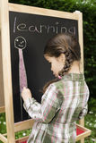 Little girl learning. Little girl drawing on blackboard in nature, learning and have a lot of fun Royalty Free Stock Photography