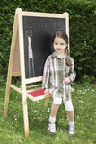 Little girl learning. Little girl drawing on blackboard in nature, learning and have a lot of fun Stock Image