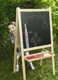 Little girl learning. Little girl drawing on blackboard in nature, learning and have a lot of fun Royalty Free Stock Photos
