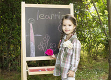 Little girl learning. Little girl drawing on blackboard in nature, learning and have a lot of fun Royalty Free Stock Photo