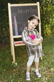Little girl learning. Little girl drawing on blackboard in nature, learning and have a lot of fun Stock Photo