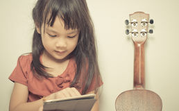 Little girl is learning how to play guitar using her tablet Royalty Free Stock Photo