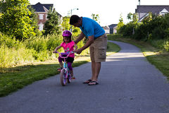 Little girl learning how to ride a bike with her dad Royalty Free Stock Photos