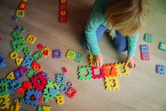 Little girl learning numbers play with puzzle. Education stock images