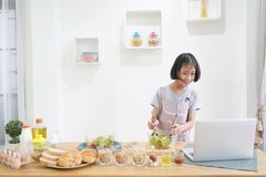 Little girl learning online cooking with using laptop computer in the kitchen royalty free stock photo