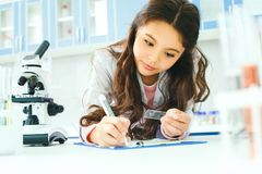 Little child with learning class in school laboratory writing results. Little girl learning in school laboratory holding samle writing results of observation royalty free stock image