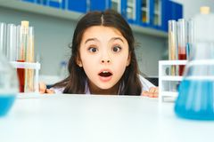 Little child with learning class in school laboratory looking camera. Little girl learning in school laboratory looking camera surprised close-up Royalty Free Stock Photos