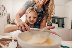 Little girl learning to make batter from her mother Stock Images