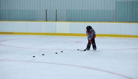 Little girl learning to play hockey. A five year old girl in hockey helmet, skates and hockey stick on ice skating rink with a row of pucks lined up for shooting Royalty Free Stock Image
