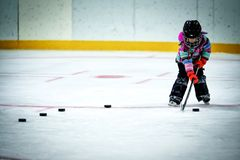 Little girl learning to play hockey. A kindergarten aged little girl in ski pants and winter jacket and helmet lining up a row of hockey pucks to practice Stock Photography
