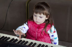Little girl learning to play piano. Concept of music study and creative hobby Stock Photography