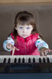 Little girl learning to play piano. Concept of music study and creative hobby Royalty Free Stock Images