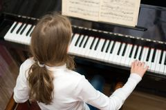 Little girl play the piano royalty free stock photo