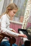 Little girl play the piano stock images