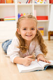 Little girl learning to read. Little girl enjoying a book, reading on the floor Royalty Free Stock Photos