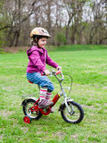 Little girl learning to ride a bicycle Stock Photos