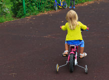 Little girl learning to ride bike Stock Images