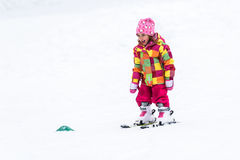 Little girl is learning to ski in ski resort. Stock Photo