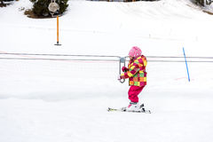 Little girl is learning to ski in ski resort. Royalty Free Stock Photography