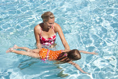 Little Girl learning to swim. Swimming lessons. Mother teaching young daughter to swim in an outdoor pool Stock Photography