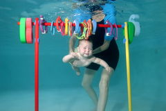 Little girl learning to swim. In a swimming pool, mother holding Royalty Free Stock Photo