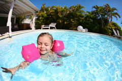 Little girl learning to swim on a hot sunny day Stock Image
