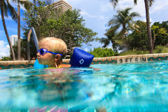 Little girl learning to swim in pool Royalty Free Stock Photos