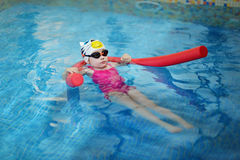 Little girl learning to swim with pool noodle Royalty Free Stock Image