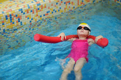 Little girl learning to swim with pool noodle Royalty Free Stock Images