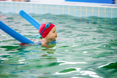 Little girl learning to swim in a pool. Toddler girl learning to swim with a pool noodle in a seawater swimming pool Royalty Free Stock Photography